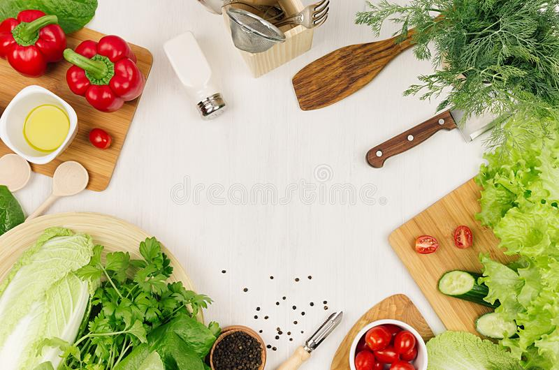 Frame of fresh green salad, red paprika, cherry tomato, pepper, oil and kitchenware on soft white wooden board. stock photos