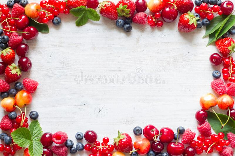 Frame with fresh summer berries mix, strawberries, raspberries, cherries, blueberries and currants royalty free stock images