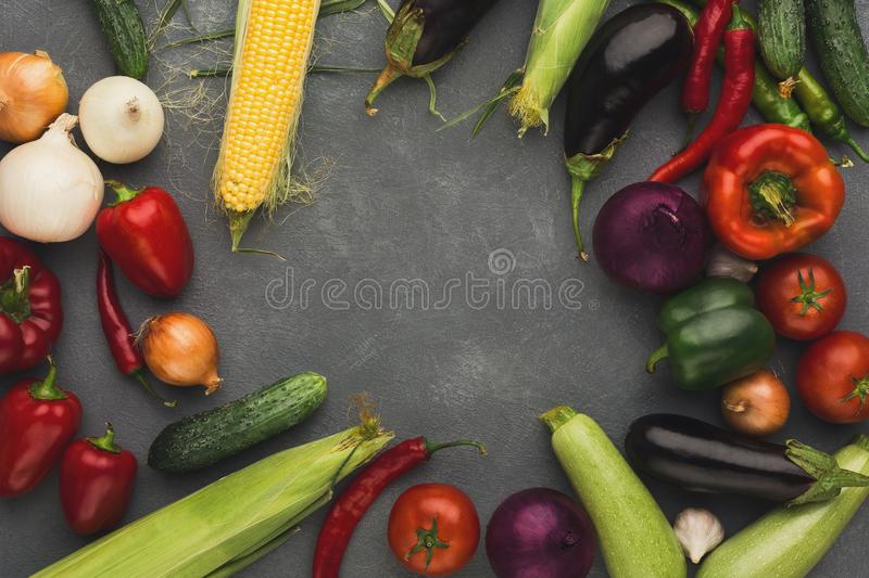 Frame of fresh vegetables on grey backgroundwith copy space. Frame of fresh organic vegetables on grey background. Healthy natural food on rustic wooden table stock photo