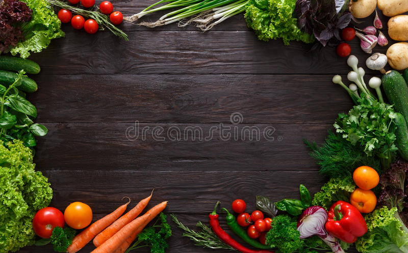 Frame of fresh vegetables on wooden background with copy space. Frame of fresh organic vegetables on wood background. Healthy natural food on rustic wooden table royalty free stock photo