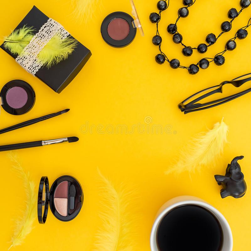 Frame with gift box, glasses, cosmetics, bijouterie and accessories with mug of coffee on yellow background. Blogger concept. Flat. Lay royalty free stock image