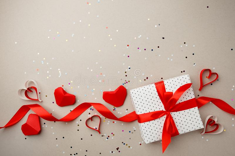 Frame of gift box and hearts and confetti on gray background, valentine mother day closeup. Flat lay, top view.  royalty free stock photos