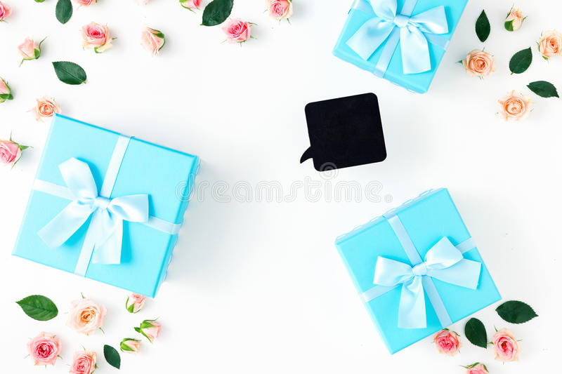 Frame gift boxes, pink roses on white background flat lay royalty free stock photo