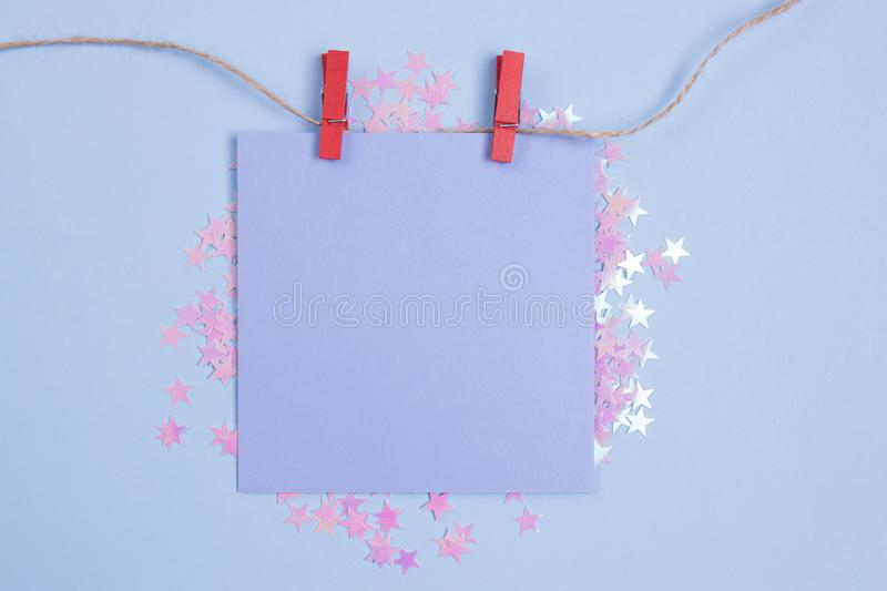 Frame of glitter stars with blue blank card mockup on blue background. Flat lay. Place for your text.  royalty free stock photo