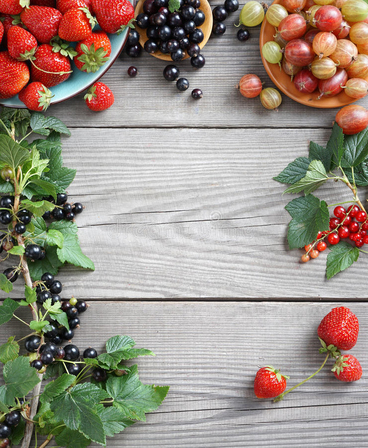 Frame from gooseberry, strawberry and branches with currants on wooden background royalty free stock image