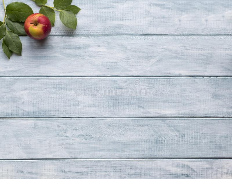 Frame of green leaves and apple on wooden vintage boards. copy space. Frame of green leaves and apple on wooden vintage boards. Place for text royalty free stock photo