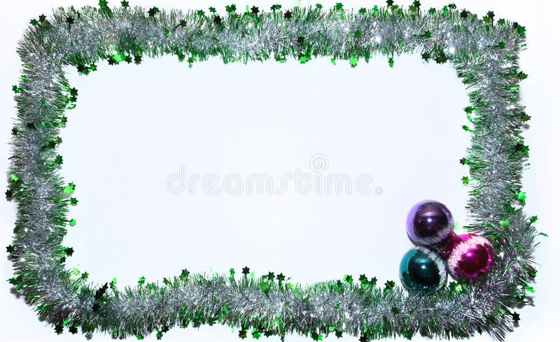 Frame of green and silver Christmas tinsel with colored glass balls. White background. Pattern stock images