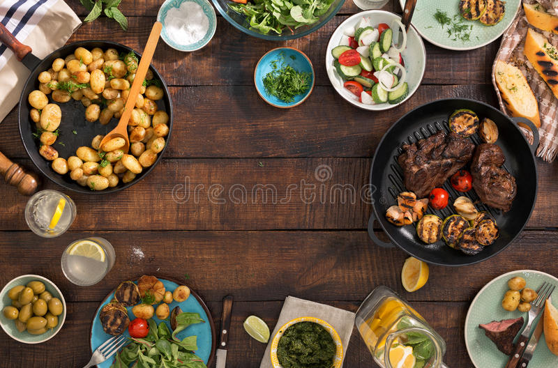 Frame of grilled steak, vegetables, potatoes, salad, snacks, homemade lemonade. Frame of grilled steak, grilled vegetables, potatoes, salad, different snacks and royalty free stock photography