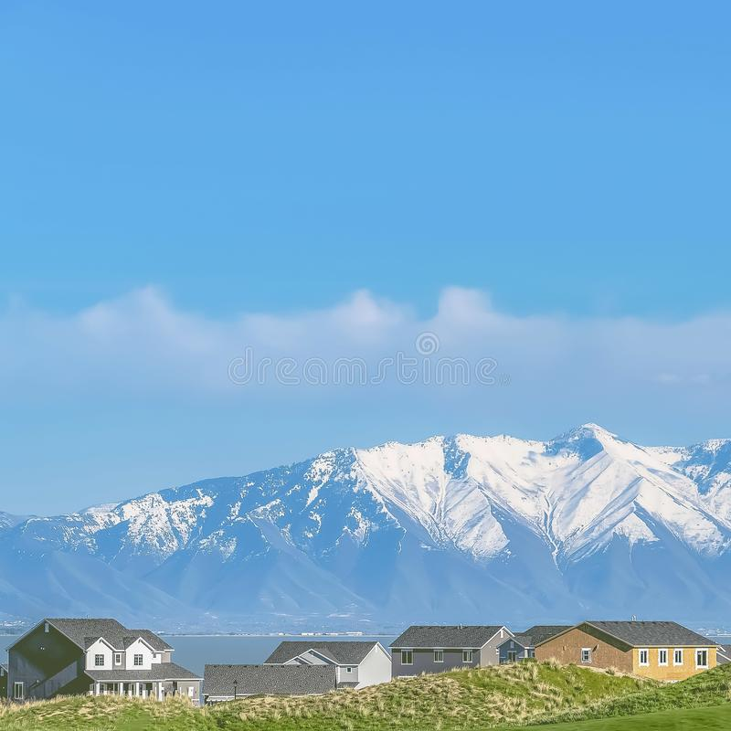 Frame Homes and grassy field with snow covered mountain and blue sky background. Square frame Homes and grassy field with snow covered mountain and blue sky royalty free stock photos