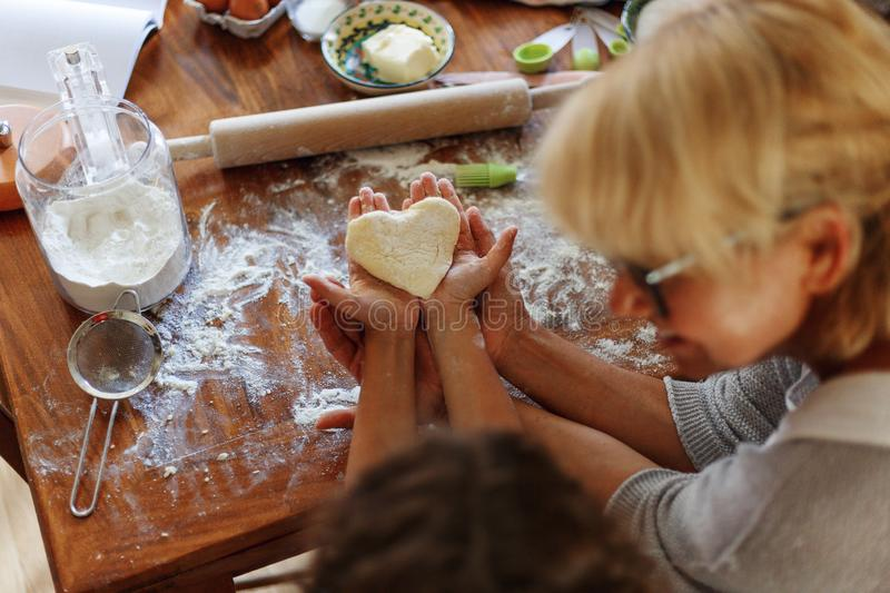 Frame image of a female and kid hands holding dough in heart shape top view. Baking ingredients on the dark table royalty free stock photos