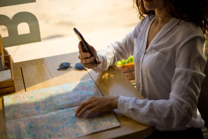 Frame image of women`s hands holding a mobile phone, uses mobile phone in cafe, above of paper city map. Copy space. royalty free stock photos