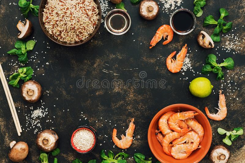 Frame with the ingredients of Asian food. Crude brown rice,shrimps, mushrooms. Copy space, top view. The concept of Asian cuisine stock images