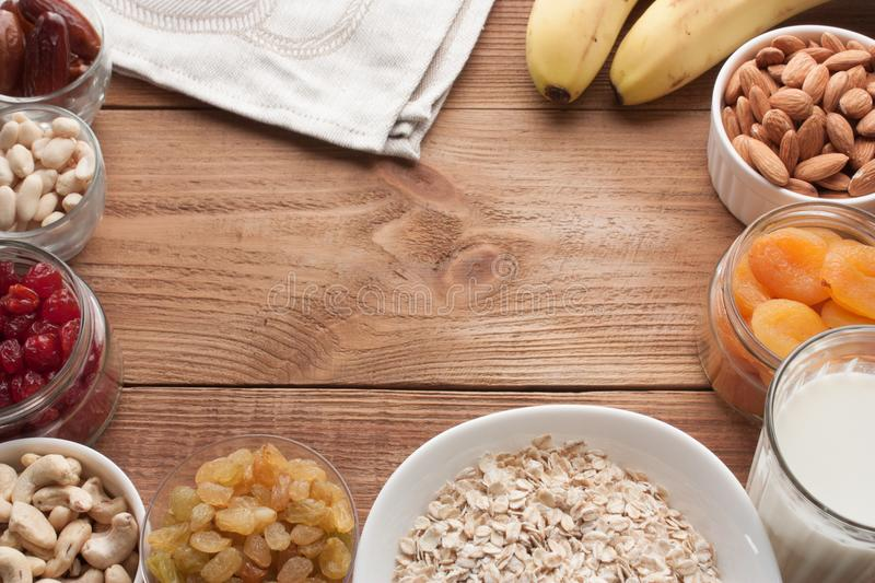 Frame of ingredients for healthy breakfast. Fresh and dried fruits, nuts, milk. Copy space on wooden table. royalty free stock photography