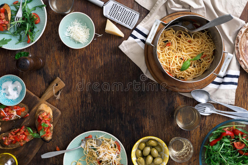 Frame of Italian pasta, snacks end wine on wooden table. Frame of Italian pasta, snacks end wine on a wooden table. Italian dinner table concept royalty free stock photography