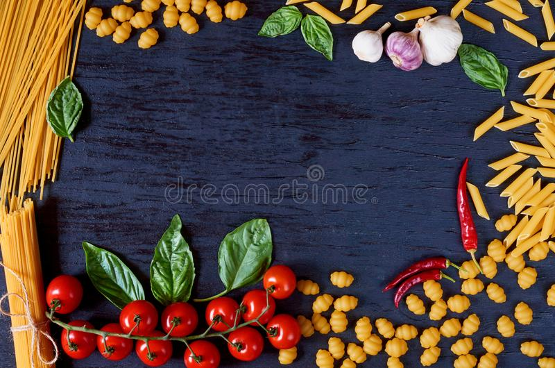 Frame of Italian traditional food, spices and ingredients for cooking as basil, cherry tomatoes, garlic and various pasta. On black wooden background. Top view royalty free stock photo