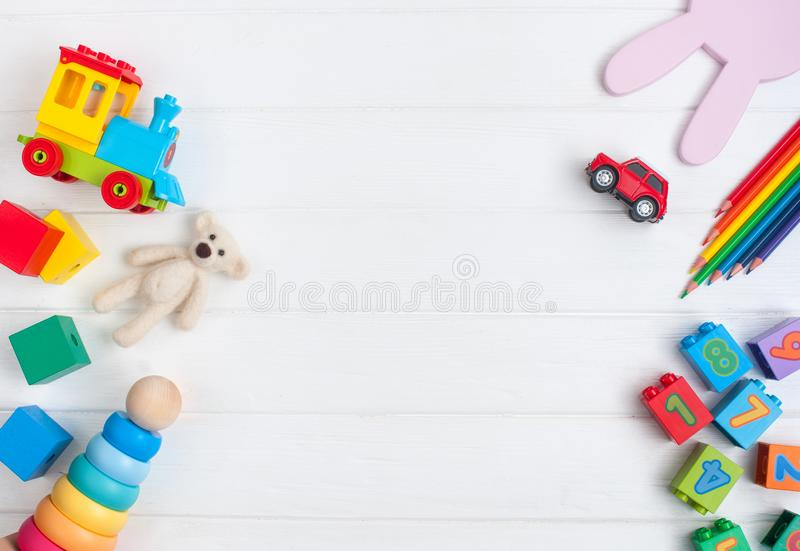 Frame of kids toys on white wooden background with copy space royalty free stock photography