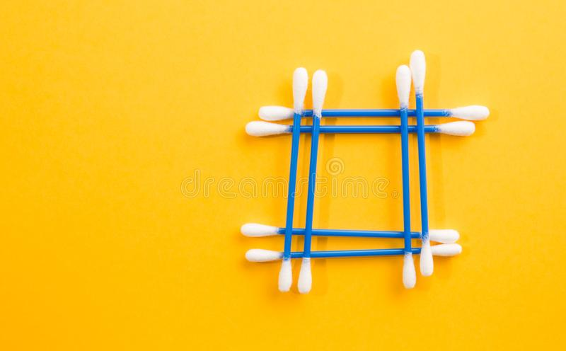 Frame made of blue cotton buds on yellow background stock photos