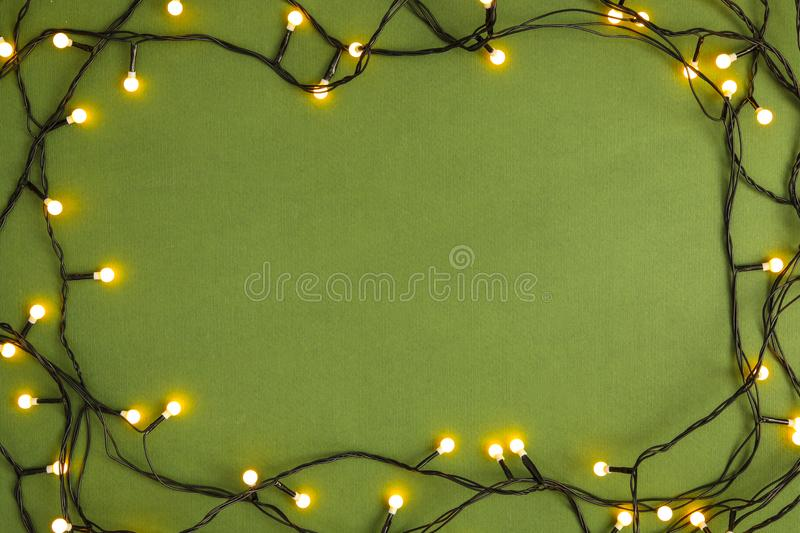 Frame made with Christmas lights on green background. Top view. Space for text stock photography