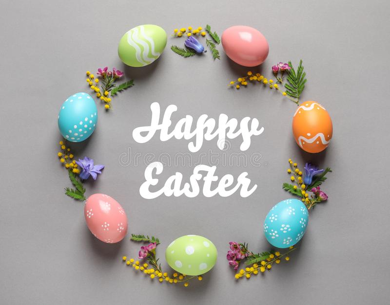 Frame made of colorful painted eggs and text Happy Easter on color background. Top view stock photo