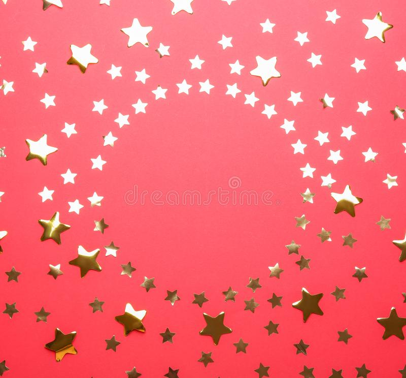 Frame made of confetti  with space for text on red background, top view. Christmas celebration. Frame made of confetti stars with space for text on red royalty free stock image
