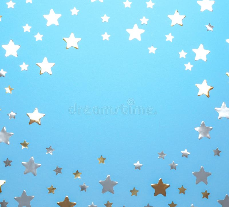 Frame made of confetti stars with space for text on blue background. Christmas celebration. Frame made of confetti stars with space for text on blue background stock photo