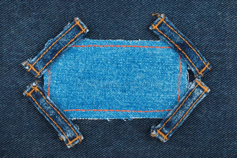 Frame made of denim with four straps of jeans, lies on the dark denim. Top view royalty free stock photos