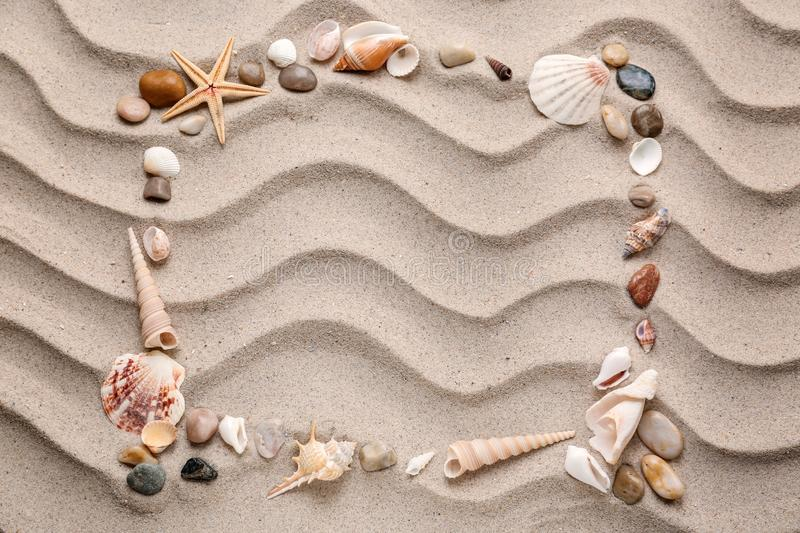 Frame made of different sea shells and stones on sand stock image