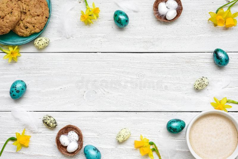 Frame made of easter eggs, cup of cappuccino, spring flowers and biscuits on white wooden background. easter composition stock photography