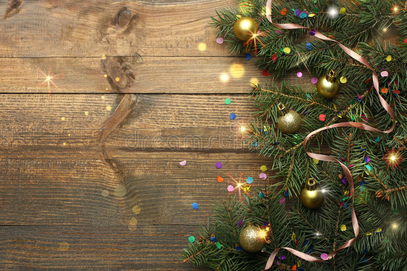 Frame made of fir branches. Fir-tree branch and Christmas toys with confetti on wooden background stock photography