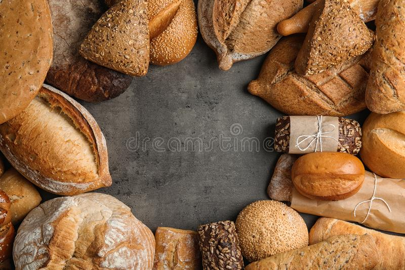 Frame made with fresh bread on grey background. Flat lay. Space for text stock image