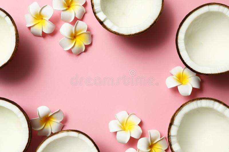 Frame made of fresh coconut halves and flowers on pink background, flat lay. Space for royalty free stock images