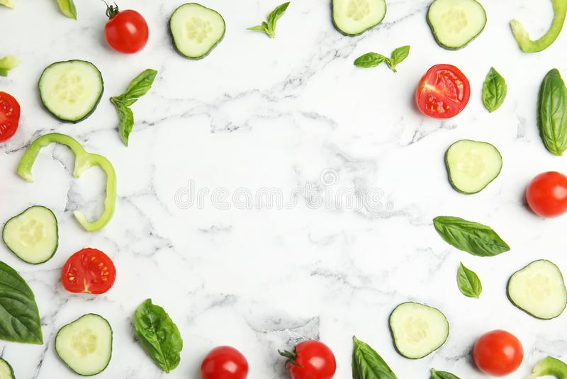 Frame made with fresh salad ingredients on white marble table. Space for text. Frame made with fresh salad ingredients on white marble table, flat lay. Space for stock photography