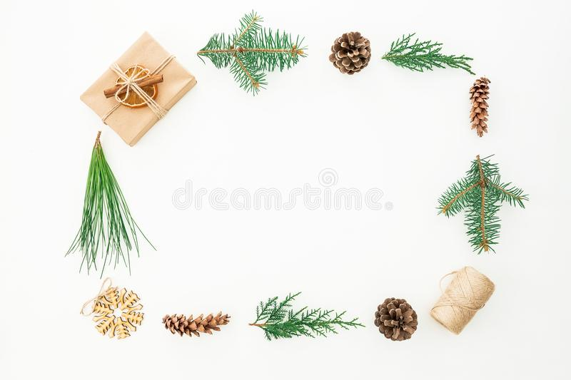 Frame made of gift box, branches of tree and pine cones on white background. Christmas or New year composition. Flat lay. Top view stock photography