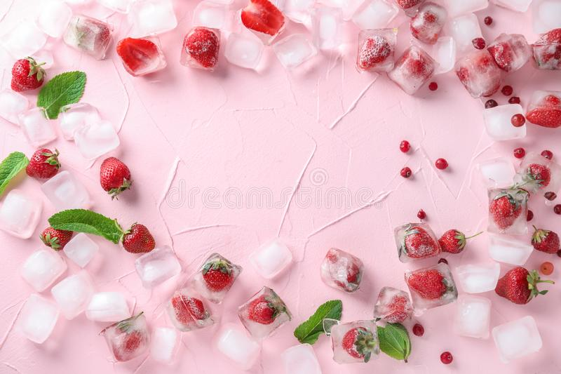 Frame made of ice cubes with strawberries on color background stock images