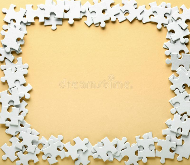 Frame made of jigsaw puzzle pieces on color background stock image