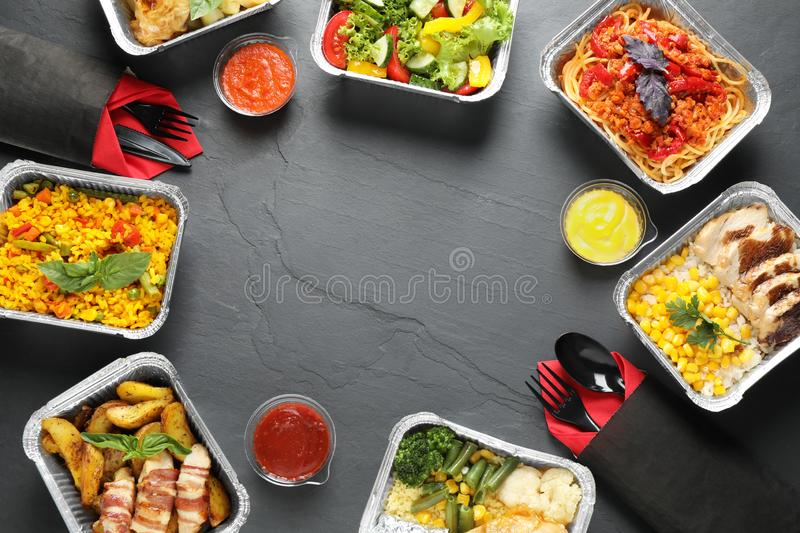 Frame made of lunchboxes on grey table, space for text. Healthy food delivery stock image