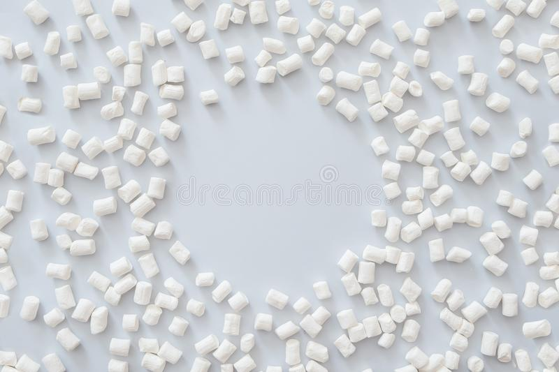 Frame made of marshmallow on pastel blue background. Flat lay, top view, copy space. Winter concept. stock photography