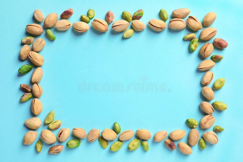 Frame made of organic pistachio nuts, flat lay. Space for text stock images