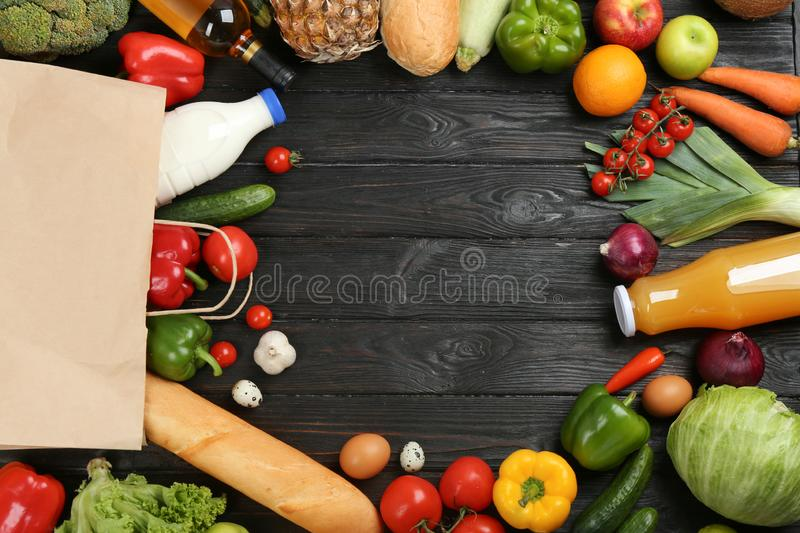 Frame made with  paper bag and groceries on black wooden background, top view. Space for text royalty free stock photography