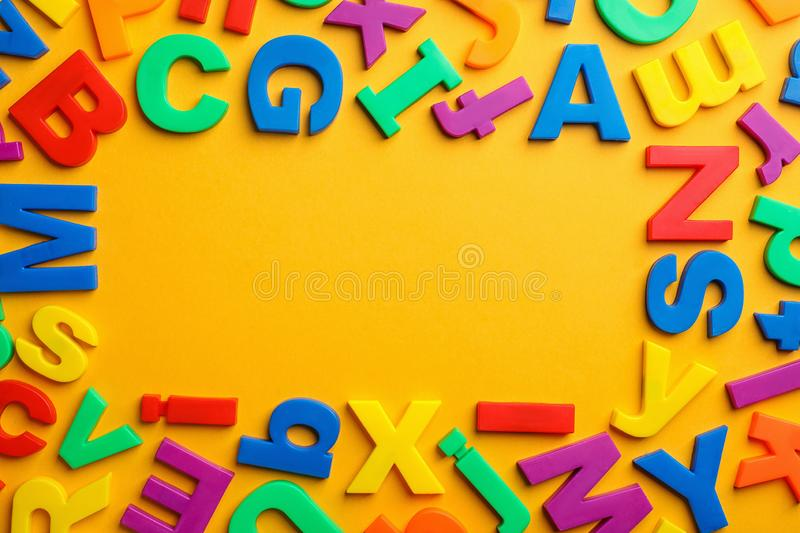 Frame made of plastic magnetic letters on color background. Top view with space for text royalty free stock images