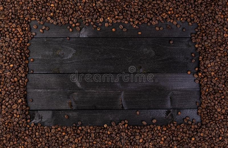 Frame made of roasted coffee beans on black wooden background, top view royalty free stock photography
