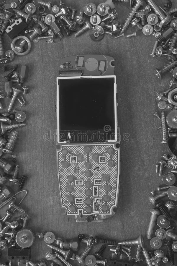 Frame made of screws on a desk around broken cell mobile phone. Frame made of screws, bolts on a desk around broken cell mobile phone in black and white royalty free stock image