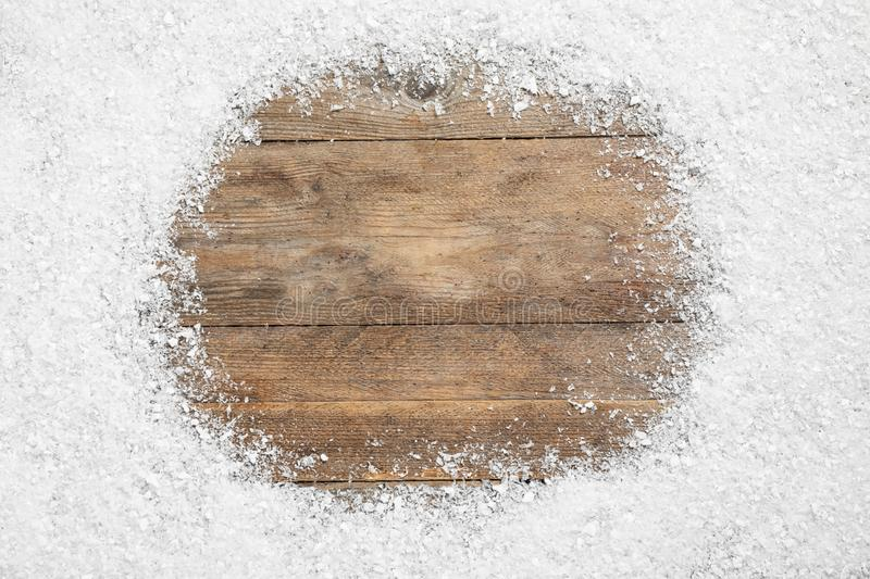 Frame made of on wooden background, top view with space for text. Christmas season. Frame made of snow on wooden background, top view with space for text stock photo