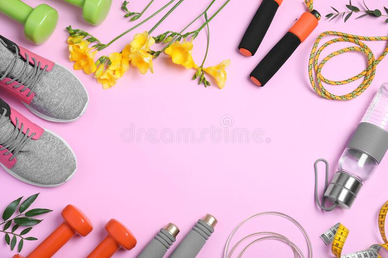 Frame made with spring flowers and sports items on pink, flat lay. Space for text. Frame made with spring flowers and sports items on pink background, flat lay stock image