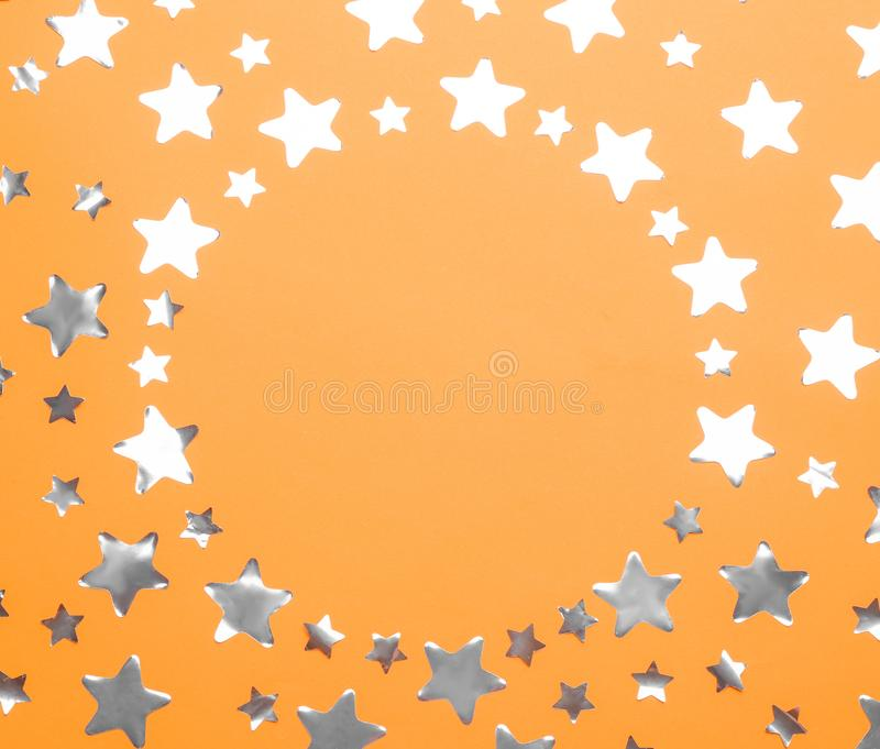 Frame made of stars with space for text on orange background, top view. Christmas celebration. Frame made of confetti stars with space for text on orange stock photo