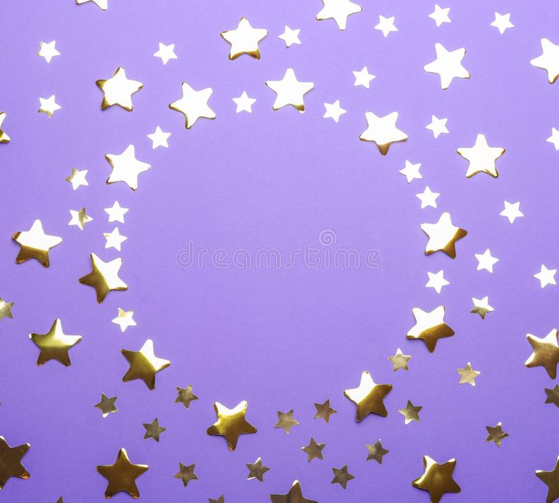 Frame made of stars with space for text on violet background, top view. Christmas celebration. Frame made of confetti stars with space for text on violet royalty free stock photography