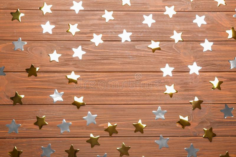 Frame made of  stars with space for text on wooden background, top view. Christmas celebration stock image