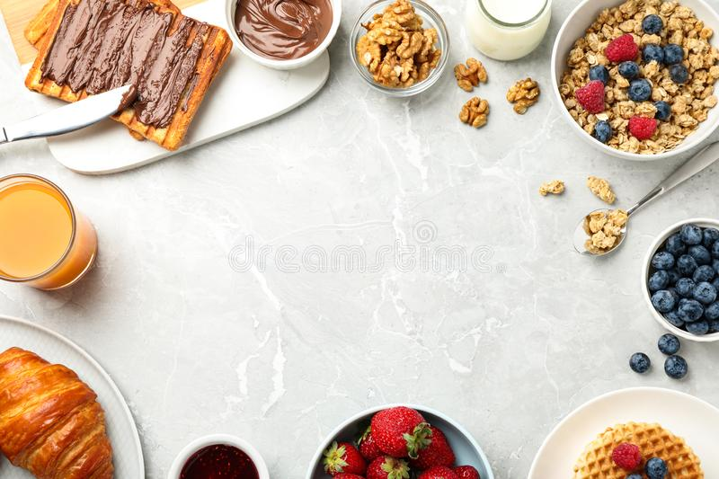 Frame made with tasty breakfast on light grey marble table. Space for text royalty free stock photography