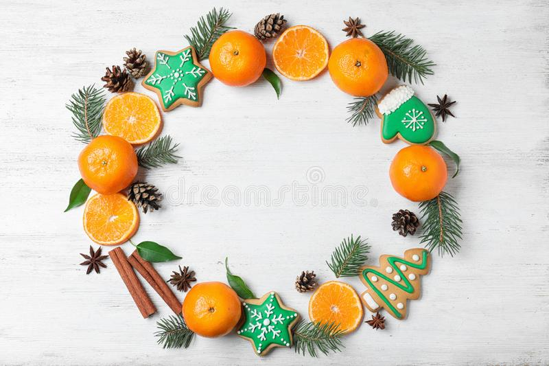 Frame made with tasty Christmas cookies and tangerines on white wooden background, flat lay. Space for text royalty free stock photography