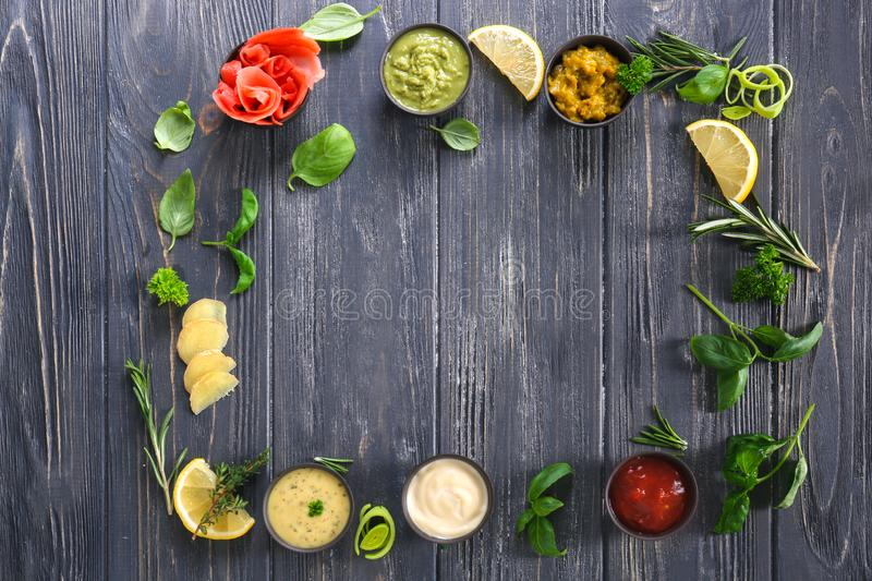 Frame made of tasty sauces and herbs on wooden table royalty free stock photography